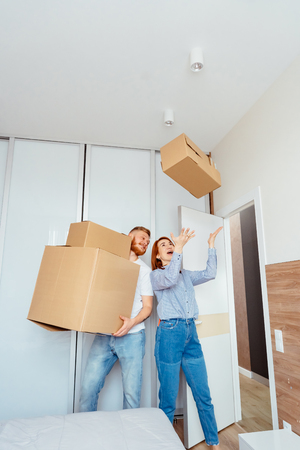 Happy couple holding cardboard boxes and moving to new place