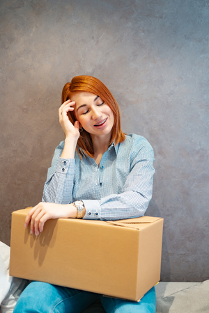 Young woman moving into new apartment holding cardboard boxes Imagens