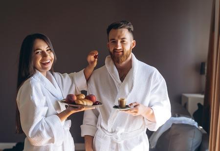 The guy and the girl bathrobe, girl feeds the guy fruit Stock Photo