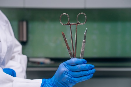 A rubber gloved hand holds two scalpels and a clamp, close angle Banco de Imagens - 120737719