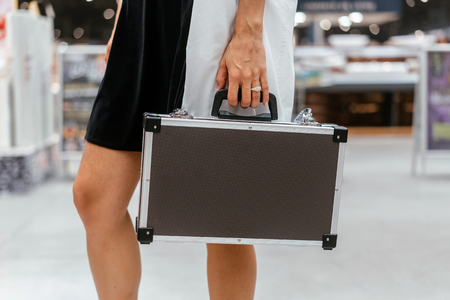 The girl holds a small aluminum case