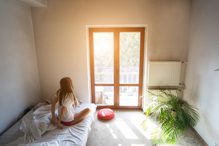Young woman sitting on bed and looking through the window.