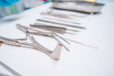Several surgical instruments lie on a white table 版權商用圖片