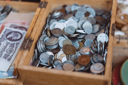 Old coins of different denominations are in a small wooden box Stok Fotoğraf