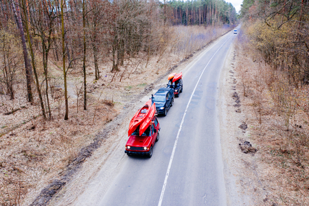 Several cars with kayaks on roof rack driving on the road among trees