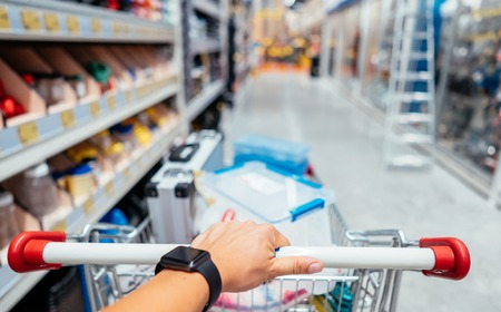 Human Hand Close Up With Shopping Cart in a Supermarket Walking Trough the Aisle 版權商用圖片