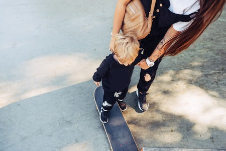 Young mother teaches her little boy to ride a skateboard