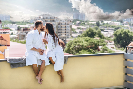 flirting couple with sparkling wine on a roof