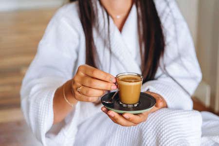 Close-up image of a woman holding a coffee mug.