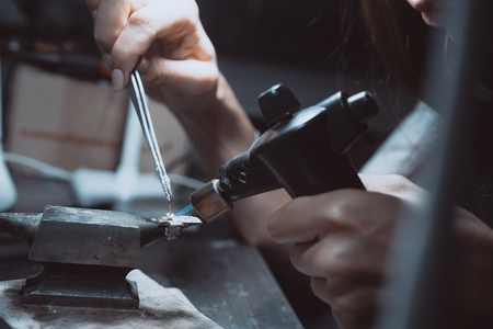 In the workshop, a woman jeweler is busy soldering jewelry