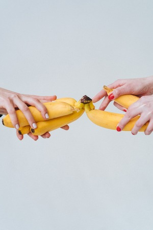 Two pairs of hands holding a few bananas Фото со стока