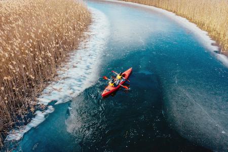 Dos hombre atlético flota en un barco rojo en el río. Foto de archivo