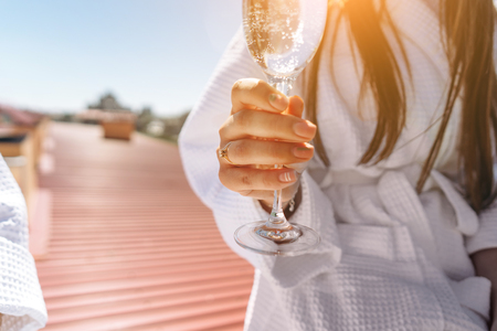 flirting couple with sparkling wine on a roof, close angle
