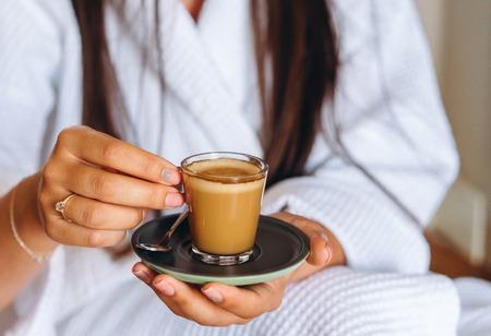 Close-up image of a woman holding a coffee mug. Small saucer with mug and spoon