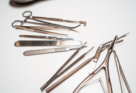 Several surgical instruments lie on a white table Banco de Imagens - 122265741