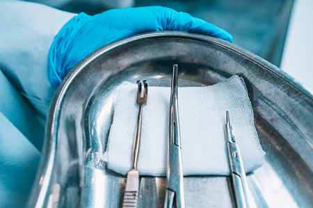 Several surgical instruments lie on a tray