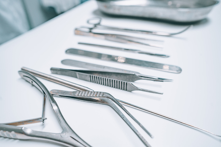 Several surgical instruments lie on a white table Stock Photo