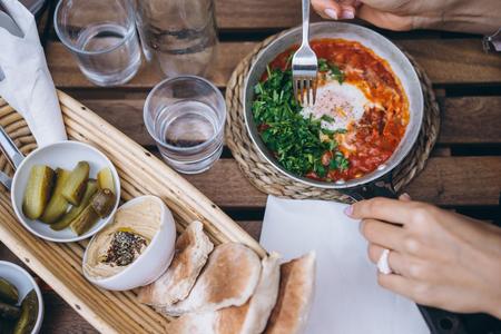 Shakshuka, Fried Eggs in Tomato Sauce on the Table. Street Restaurant Stock Photo