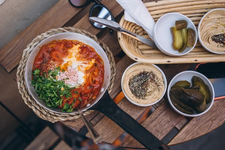 Shakshuka, Fried Eggs in Tomato Sauce on the Table. Street Restaurant Stock Photo