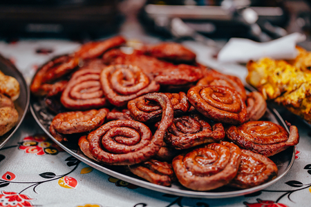 Roasted spiral sausages on a plate, close angle.