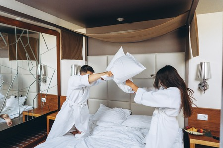 Cheerful couple have fun in the bedroom fighting with big pillows at home Banco de Imagens - 123209536