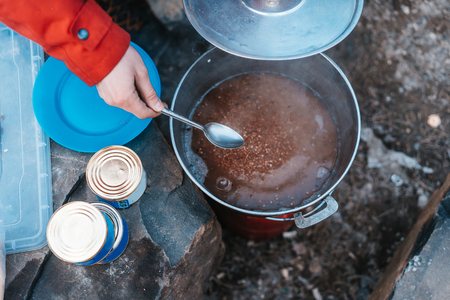 Camper preparing meal in large kettle on campfire