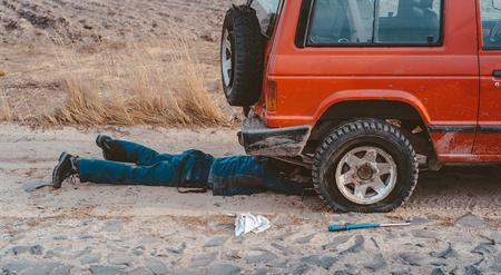 man lies under a 4x4 car on a dirt road Stock Photo - 123209898