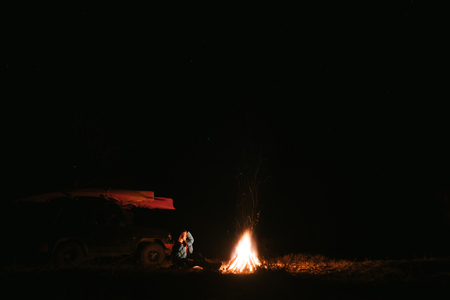 Woman sitting and getting warm near the bonfire in the night forest.