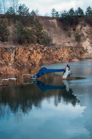 Flooded excavator in a large lake near the basaltic quarry