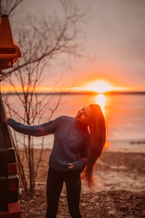 Woman enjoying time relaxing by the beautiful lake at sunrise.