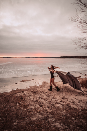 Beautiful young girl in a swimsuit on the shore of a frozen lake