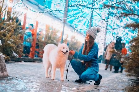 Una giovane donna accucciata accanto a un cane in una strada d'inverno.