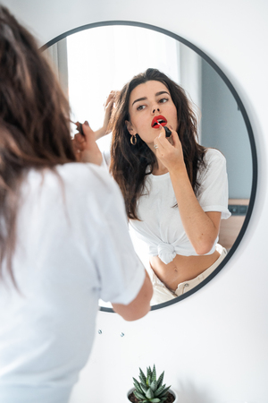 Young woman applying lipstick looking at mirror Фото со стока