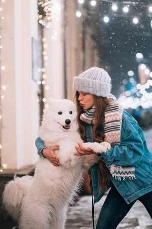 A woman is hugging her dog on a night street.