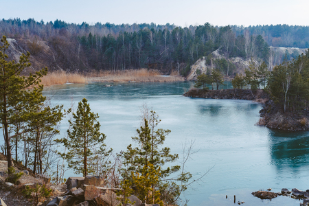 Beautiful quarry, the lake is covered with thin ice Stok Fotoğraf