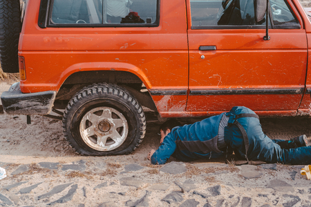 man lies under a 4x4 car on a dirt road Imagens
