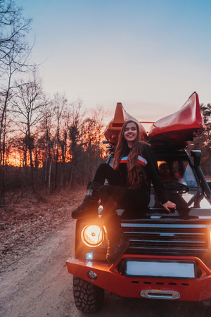 Woman sitting on front on a hood 4x4 terrain vehicle.
