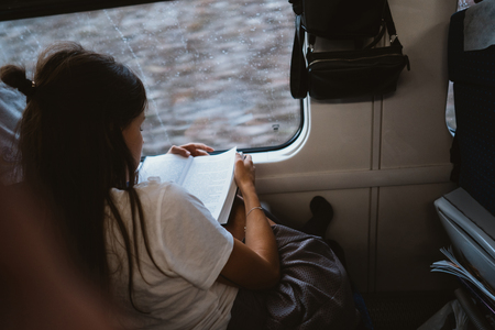 Young happy woman sitting in city bus