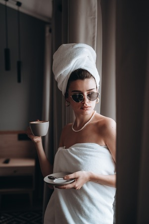 Girl wrapped in a towel drinking coffee