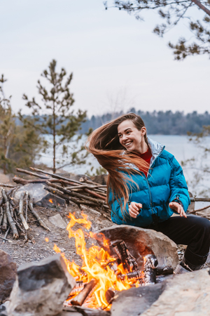 Happy young brunette girl sitting next to bonfire