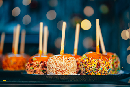 Apples in caramel and sprinkles. Street food. Imagens