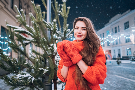Young woman posing near the Christmas tree on the street Imagens