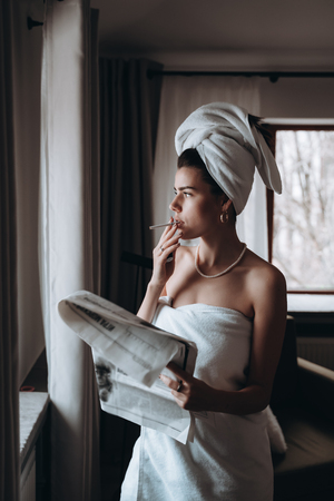 Beautiful young woman in a towel smokes a cigarette and reads newspaper