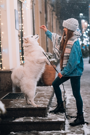 Photo of a young woman and a white dog who shows tricks on an street Imagens