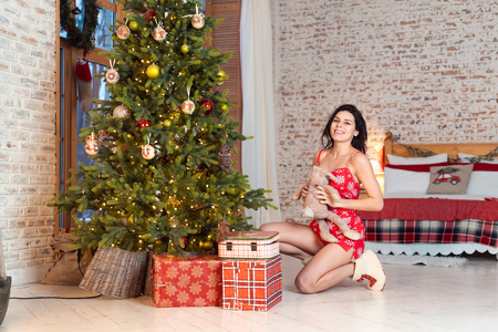 Beautiful young woman playing with a teddy bear by the Christmas tree Imagens