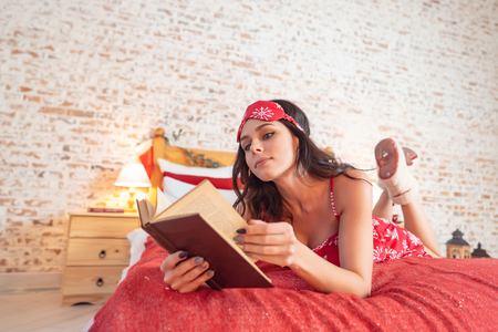 Appealing long-haired woman in red pajamas resting on bed Imagens