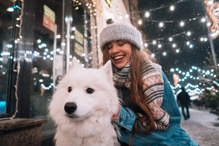 A young woman crouched beside a dog on a winter street.