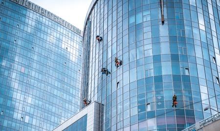 Kilku pracowników myje okna w biurowcu