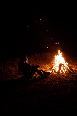 Lonely young woman sitting and getting warm near the bonfire in the night forest. Young girl alone