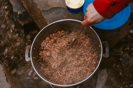Camper preparing meal in large kettle on campfire from above